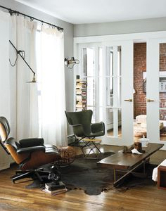 In the living room, an Eames lounge chair is matched with a Richard Conover–designed fiberglass chair in similar proportions. A custom coffee table by Asher Israelow com-plements the industrial lighting by Workstead, affixed to walls painted in Farrow and Ball's Manor House Gray. The sliding doors leading into the home office were fabricated by Markus Bartenschlager.  Courtesy of matthew williams.