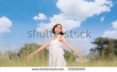 Vintage tone. Young woman in white dress relax on the dry grass field in summer time.