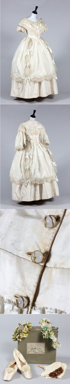 Wedding Dress, 1857, day bodice with buttons coiled with metal snakes, short sleeved evening bodice, over-skirt and plain silk underskirt, shoes, a wax bridal wreath, a later silk floral wreath and a dried floral bridesmaid posy. Although a snake motif might seem an unusual adornment for a bridal gown, in the 19th century it was thought to symbolise wisdom and eternity. Prince Albert presented Queen Victoria with an emerald inset snake ring at their engagement which further fuelled the…