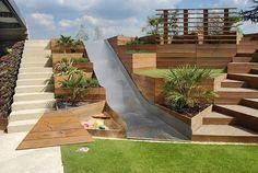 terrasses, bac à sable et toboggan en aménagement cour arrière moderne