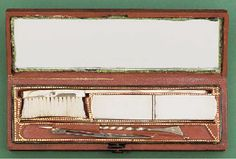 A French 19th-Century gold oral hygiene set,  including: a gold tooth-brush, tooth-powder box, toothpick and [?]earscoop, with a mirror on the inside lid, contained in moroccan red leather case -- 4 7/8in. (12.4cm.) long