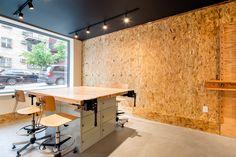 art studio in residential building, art work table, art stools, black ceilings, OSB board walls, wall hung art easels