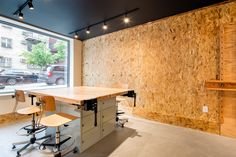 art studio in residential building, art work table, art stools, black ceilings, OSB board walls, wall hung art easels