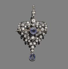 A sapphire and diamond pendant/brooch, circa 1900.  The openwork cartouche designed as a series of cushion-shaped and old brilliant-cut diamond scrolls, centrally-set with a circular-cut sapphire in millegrain-setting, suspending a similarly-set pear-shaped sapphire, mounted in silver and gold, to a later flat curb-link chain, diamonds approx. 0.60ct total, later brooch fitting, lengths: pendant 4.5cm, chain 45.5cm