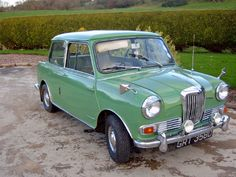 Riley Elf, British Motors Corp. parked by a hedge. Porcelain green, Glen green or another green. Body color top. Released in 1961 as more luxurious versions of the Mini, both the Wolseley Hornet and the Riley Elf had longer, slightly finned rear wings and larger boots that gave the cars a more traditional three-box design.