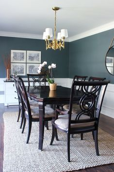 Dark walls and brass light fixture in the dining room.