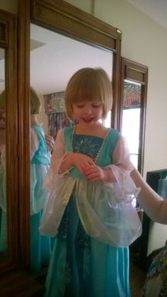 My daughter chose the colors, fabric, pattern style elements to build a Frozen dress that was part Elsa. I added vintage rhinestone trim around neckline. I cut around the snowflakes in the contrast fabric  and tacked in front of skirt instead of removing in the seam.