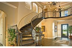 A graceful staircase and balcony with wrought iron balusters make a dramatic entry to this elegant home. Standard Pacific Homes, near Ft. Worth.