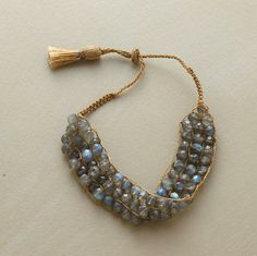 "Three rows of faceted labradorites are woven by hand on a delicate ladder of roped gold thread. Designed by Lena Skadegard with a sliding tassel closure. Adjustable 6"" to 8""L."