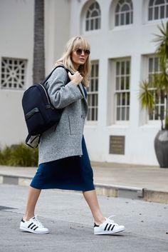 Oversized coat, slip dress, black backpack and Adidas sneakers.