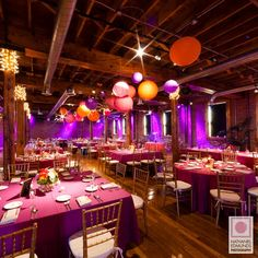 Hanging lanterns in shades of purple, blue, green, and white in varying sizes.