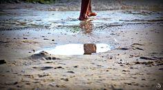 Pés molhados sobre a areia da praia quente.