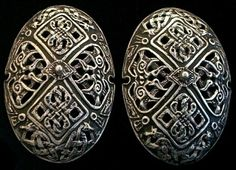 Sterling silver oval brooches based on find from Snasen, Norway 8th - 10th Century. The most characteristic items of female Viking  jewelry are the pairs of Oval Brooches, sometimes called Tortoise Brooches, from their shape, found in many female graves from the Viking Age. Brooches were sometimes chained together. The chains supported utilitarian objects such as tweezers, ear spoon,  scissors and a saex (knife).  Sometimes the Brooches suspended strands of beads of glass, silver, amber or…