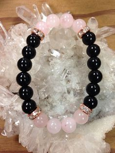 Black Onyx and Rose Quartz beaded bracelet with faux rose gold details. 8 mm beads. Black Onyx - It can help release negative emotions such as sorrow and grief. It is used to end unhappy or bothersome relationships. Onyx guards against negativity Rose Quartz - stone of love Please