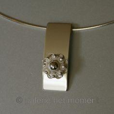 Zilveren hanger met Zeeuwse knop op gebogen plaatje