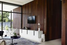 Swinburne Avenue Residence living room by Doherty Lynch. Bespoke joinery, spotted gum cladding and large black framed windows.