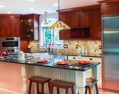 Large kitchen island, granite countertops, white cabinets, seating for three, cook top build in.