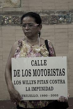 Doña Amanda sostiene la placa de la calle de los motoristas donde pertenecía su esposo.