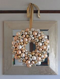 Silver & gold Christmas wreathe. dollar ornaments from the dollar store, spray paint some with glitter, hang over living room mirror