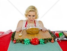 young woman looking at paste of christmas cookies. - Young woman looking at paste of christmas cookies against white background.