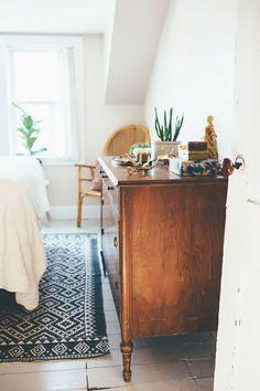 wood dresser, white linens, plants