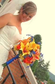 Orange and Blue flowers wedding bouquet. I used fake flowers for this floral arrangement--stays perfect until the day of the wedding, and forever after! No need to preserve. I tied the stem with blue ribbon and added an antique brooch of my Grandmother's. The bouquet comprised tiger lilies (my favorite), gerber daisies, chrysanthemums, day lilies