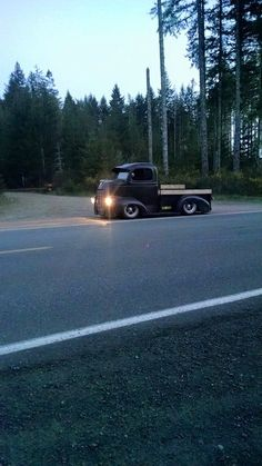 slammed COE in satin black, long bed, and wooden stake sides sporting narrow white wall tires and a visor all out for an evening drive. Pic 1