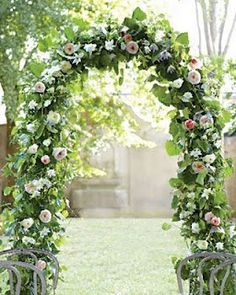 To inexpensively embellish an arch, go heavy on the foliage.  Then slip in a few of the same flowers used in your bouquet to unify the vibe. Here, roses and clematis adorn grape ivy and passionflower vines woven around a Tuscan Wedding iron arbor