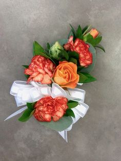 Orange rose and carnation corsage by Nancy at Belton Hyvee.