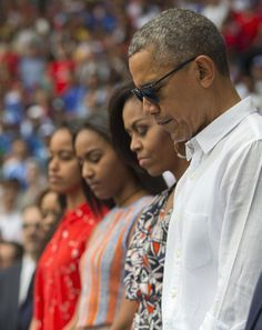 President Barack Obama and family pause during a moment of silence before the…