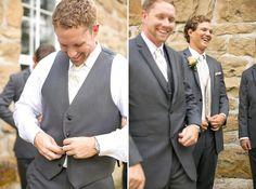 groom buttons up gray vest outside church @myweddingdotcom