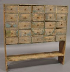"""Apothecary Bucket BenchTwenty-five small drawers with wood pulls, stretcher shelf, traces of green, white and blue paint, 59""""t., 11 3/4""""d., 57""""w."""