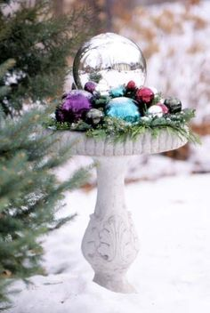 colorful bulbs and evergreens in birdbath = charming holiday display