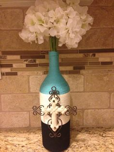 This lovely magnum size wine bottle is wrapped in teal, cream, and black yarn accented with a beautiful wrought iron and ceramic cream