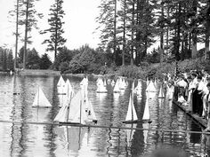 Crowd of children standing on the dock watching toy sailboats at Laurelhurst Park, Seattle, Washington | by UW Digital Collections