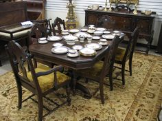 """EIGHT-PIECE WALNUT DINING SET, Baker Furniture Co., Michigan, c. 1920's, comprising: rectangular extension dining table with three 9.75"""" leaves, six dining chairs and a long sideboard."""