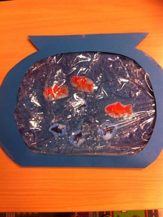 """Een zintuiglijke beleving van het woord VIS. Gemaakt van een diepvrieszakje, haargel, gelamineerde visjes en een kartonnen vissenkom. Kleine plastic visjes zouden nog beter zijn zodat je de visjes door het """"water"""" heen kan duwen . Een succes in de groep!!"""