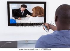 Rear View Of African Man With Remote In Front Of Television
