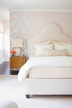 Chic, pink bedroom features a wall clad in silver and pale pink floral wallpaper lined with a cream arched bed dressed in white and pink bedding placed next to a curved wood nightstand and a white stone lamp. Pink Bedrooms, Pink Wallpaper Bedroom, Pink Room, Wallpaper Bedroom Feature Wall, Feature Wall Bedroom, Pale Pink Bedrooms, Grey And Gold Bedroom, Pink Master Bedroom, Cream And Grey Bedroom