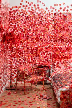 yayoi kusama obliterates a room with a 'virus' of beautiful red flowers