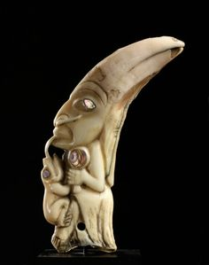 This amulet, of a shaman holding a rattle (typically used in a healing ritual) and connected at the tongue with a land otter, depicts the connection between a shaman and his animal spirit helper