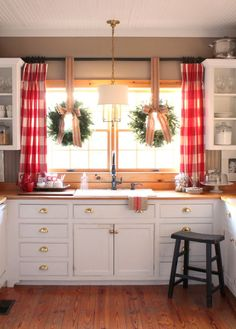 Kitchen for Christmas red buffalo check drapes wreaths in window with jute bows.
