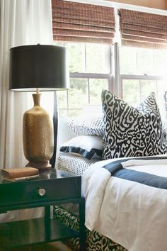 gold lamp with black shade, black nightstand, white and black mixed pattern bedding with bamboo shade