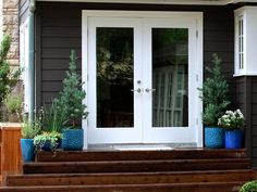 For a cool pop of color against the brown house, Royce went with ceramic planters in shades of blue, from bright turquoise to deep cobalt. Exterior House Colors, Exterior Doors, Exterior Paint, French Doors Patio, Patio Doors, Wooden Steps, Brown House, Door Makeover, White Doors