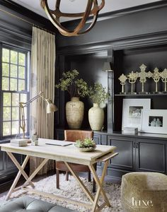 An oak desk and leather chair, both from Jayson Home, enhance the library walls featuring Benjamin Moore paint, while a Moroccan rug from Stark adds texture to the eclectic space. Draperies in a fun pattern, fabricated by Elegant Custom Draperies, soften the room's masculine feel.