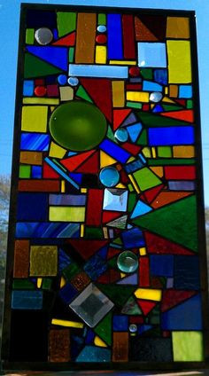 Scraps of glass, roundels, nuggets, and bevels into a glass on glass mosaic.
