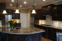 Originally light Oak cabinets, this kitchen was refinished to a custom dark stain finish with black glaze!  Gorgeous transformation!
