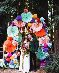 Paper fans in all kinds of bright colors. This would make a great installation on a wall for party decor.