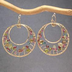 """Metal: RoseGold Hammered circles with peridot, ruby, and mandarin garnet wrapped around inside, about 2-1/4"""" long. Available in either 14K gold-filled, rose gold-filled, or sterling silver. All jewelry is entirely handmade in our studio in New York."""