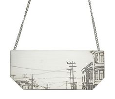 """This unusual and contemporary necklace is a real statement piece. It depicts an urban skyline scene etched in silver and is suspended from a 16"""" silver chain. Modern and unique, this piece is handmade, so the etching could vary slighty from piece to piece.  Necklace dimensions are: 8cm x 3cm"""